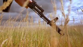 Close-up shooting, hands of soldier in camouflage are holding automatic gun weapon, while wind is blowing and high grass. Is moving, calm nature, dark skies stock footage