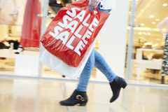 Close Up Of Shopper's Feet Carrying Bags In Shopping Mall Royalty Free Stock Images