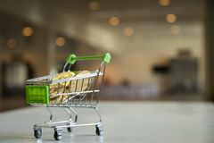 Close up shopping cart with bitcoin on white table. Blurred background, for copy space presentation product Royalty Free Stock Images
