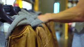 Close up shopping in fashion store Jackets on the racks Hipster style. Wear stock footage