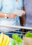 Close up of shopping list in hands of couple Royalty Free Stock Photography