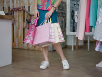 Close-up of a female buying presents. Shopping girl holding bags with clothes on a shop background. Consumerism concept. Stock Image