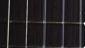 Close up shot of acoustic guitar strings. Close up shot of acoustic guitar nylon strings. Steadicam sliding shot