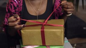 Close up shot of african female woman opening box with gift.