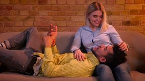 Close-up shot of african guy lying on the legs of caucasian girlfriend and talking tenderly in home atmosphere. Close-up shot of african guy lying on the legs stock video