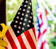 Close-up Shot of American Flag. Close-up shot of an American flag beside some yellow flowers with another American flag in the background Stock Photography