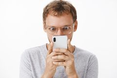 Close-up shot of amused and entertained male geek in glasses holding smartphone close to face popping eyes and staring. Intrigued at device screen reading stock photo