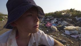 Annoyed beggar boy in dump. Close up shot of annoyed boy among rubbish in dump stock video footage