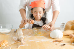 Close up shot of Asian little girl breaking the egg shell for ma Royalty Free Stock Photo