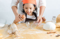 Close up shot of Asian little girl breaking the egg shell for ma Stock Photo