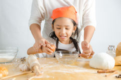 Close up shot of Asian little girl breaking the egg shell for ma Royalty Free Stock Photos