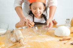 Close up shot of Asian little girl breaking the egg shell for ma Stock Image