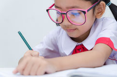 Close up shot of Asian little girl doing homework in Thai Studen Royalty Free Stock Images