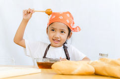 Close up shot of Asian little girl hold the honey dipper with ha Stock Photos