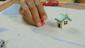 Close up shot Asian little girl pinning color pin at the map metaphor planning for transport and travel.  stock video