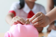 Close up shot Asian little girl in Thai student kindergarten uni. Form with mother hand putting money coin into pink piggy bank saving money for education Royalty Free Stock Photo