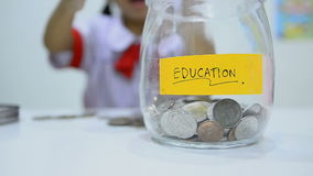 Close up shot of Asian little girl in Thai student uniform with coins and glass jar saving money concept. HD Close up shot of Asian little girl in Thai student stock video