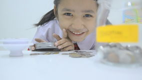 Close up shot of Asian little girl in Thai student uniform with coins and glass jar saving money concept. HD Close up shot of Asian little girl in Thai student stock video footage