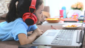Close up shot of asian little girl using laptop computer and headphone at home stock video