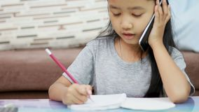 Close up shot Asian little girl using pencil doing homework and talk to smartphone.  stock video footage