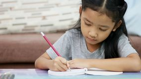 Close up shot Asian little girl using pencil write to a note book doing homework with concentration for home school and education. Concept stock video footage