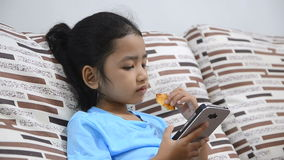 Close up shot of asian little girl using smartphone at home stock video footage