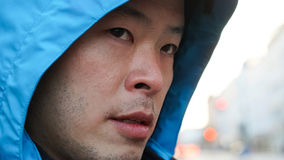 Close up shot of Asian man face with blue hood jacket. Close up of Asian man face with blue hood jacket Stock Photography