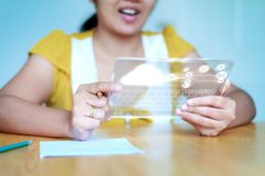 Close up shot Asian woman using clear tablet for futuristic cybe Stock Image