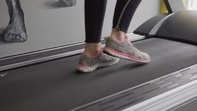 Close up shot of the athlete`s feet who is walking along the treadmill. stock video