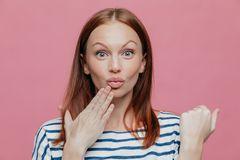Close up shot of attractive woman raises eyebrows, pouts lips, keeps hand near mouth, has brown hair, surprised by something, stock images
