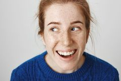 Close-up shot of attractive young caucasian female with red hair and freckles laughing and looking aside, being in royalty free stock photos