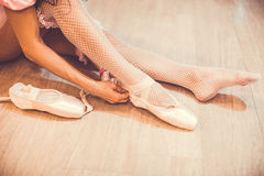 Close-up shot of a ballerina taking off the ballet shoes sitting on the floor in the studio. Close up shot of legs of sitting on the floor ballerina who laces Royalty Free Stock Photo