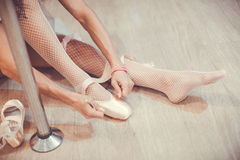 Close-up shot of a ballerina taking off the ballet shoes sitting on the floor in the studio near the pole. Close up shot of legs of sitting on the floor Royalty Free Stock Image