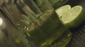 Making a Cocktail. Close-up shot of bartender`s hands cutting raw, ripe and fresh green lime on black cutting desk. Exotic fruity beverage preparation stock video