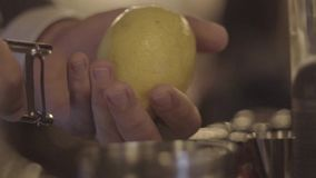 Making a Cocktail. Close-up shot of bartender`s hands cutting raw, ripe and fresh green lime on black cutting desk. Exotic fruity beverage preparation stock video footage