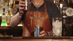 Bartender`s hands, who masterly pours liquid from the glass to another glass. Close up shot of the bartender`s hands, a man engaged in professional bartending stock footage