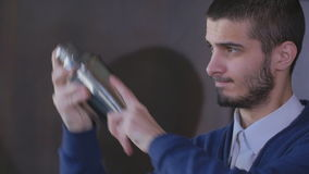 Close up shot of a bartender shaking a drink in a cocktail shaker. Bartender with shaker making cocktail in modern bar stock footage