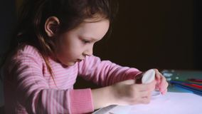 Close-up shot of beautiful little preschool European girl child in pink sweater sitting by the table gluing paper shapes stock video footage