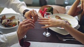 Close-up shot of beautiful ring being placed on female finger during marriage proposal at romantic dinner in restaurant. Close-up shot of beautiful ring being stock video