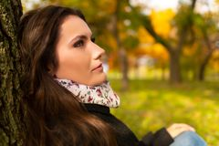 Close-up shot of a beautiful romantic girl with perfect skin and complexion, in a park autumn scenery, sitting down and
