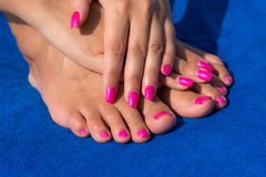 Close-up shot of beautiful women's manicure and pedicure on blue Royalty Free Stock Images