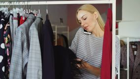 Close-up shot of beautiful young lady talking on mobile phone and choosing clothes in women`s clothing store. She is. Examining colourful stylish garments stock video footage