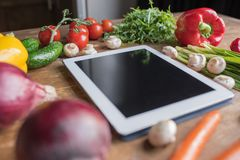close-up shot of blank tablet with vegetables stock images