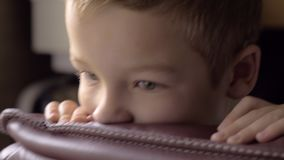 Boy swinging in the arm chair. Close-up shot of a bored child rocking in the leather arm chair leaning on its back stock video footage