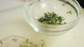 Putting herb on a bowl. A close up shot of a bowl where herb leaves are being put stock video