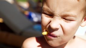 Kid having snack with french fries at the beach. Close-up shot of boy eating French fries at the beach. Child having fast food snack at the seaside stock footage