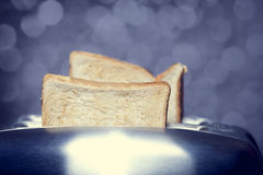 Close-up shot of a bread toast in a toaster Stock Photos