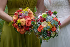 Close-up shot of bride and bridesmaid holding large colorful and sophisticated wedding bouquets. Horizontal shot of two Caucasian young women holding flower Stock Photo