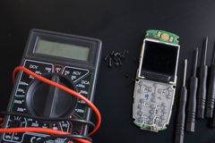Close-up shot of broken cellphone with digital multimeter. Screws and screwdrivers on black surface Stock Photography