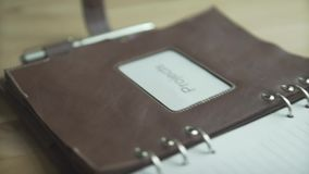 Close up shot of brown leather note pad book business project daily planner bullet journal habit tracker on wooden table. Close up shot of brown leather case stock video